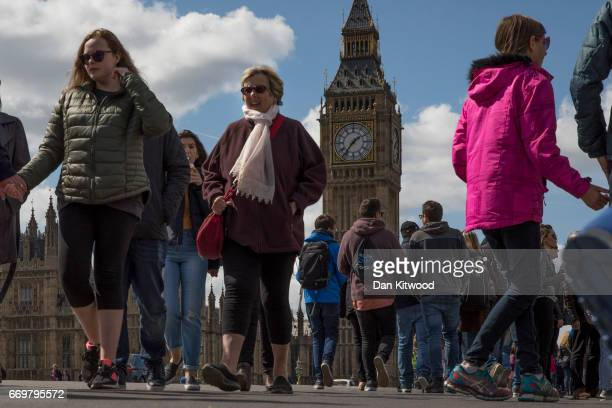 Tourists walk near the Houses of Parliament on April 18 2017 in London United Kingdom British Prime Minister Theresa May announced earlier today in a...