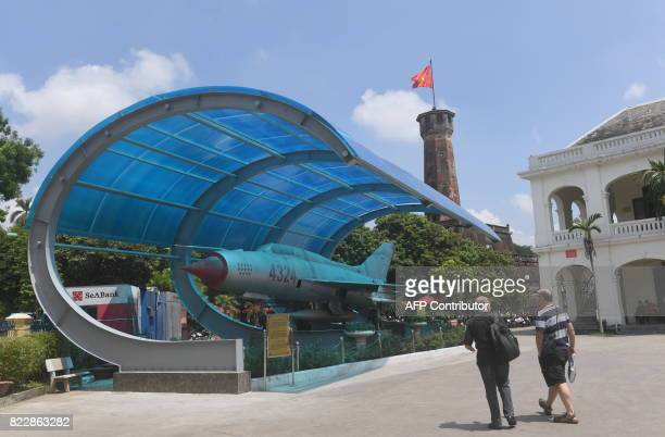 Tourists walk next to a Vietnam War Sovietmade MIG21 used by Northern Vietnam's Air Force at Hanoi's army museum on July 26 2017 / AFP PHOTO / HOANG...