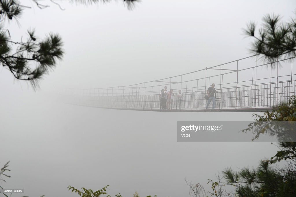 Tourists walk on a 300 metre long glassbottom bridge at a vertical height of 180 meters on September 29 2014 in Yueyang Hunan province of China
