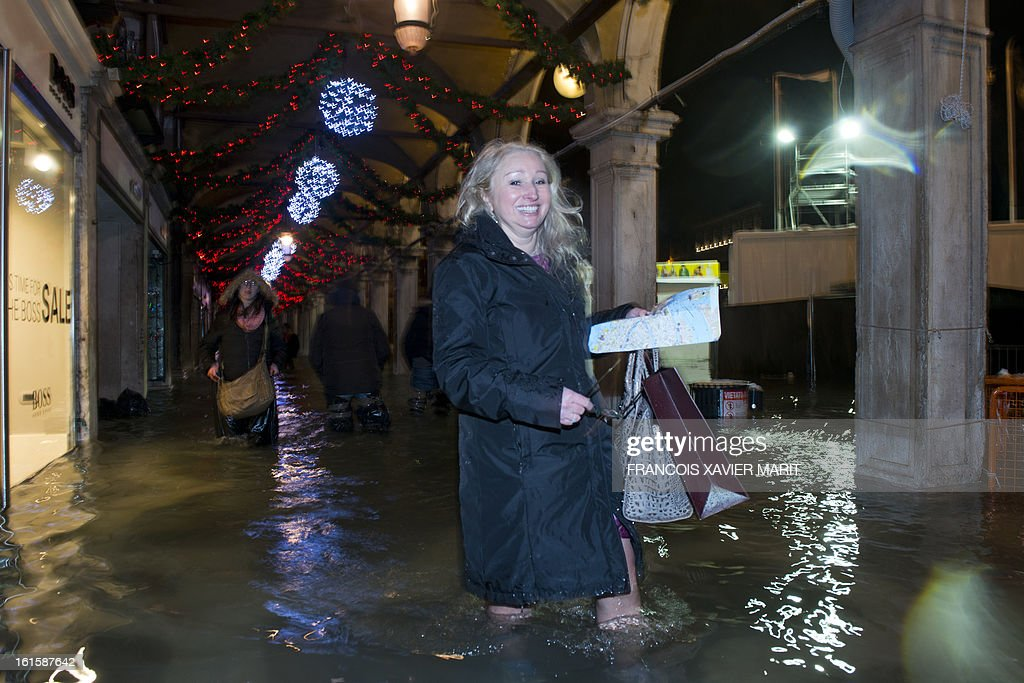 Tourists walk on a flooded St Mark's square during an acqua-alta (high-water) late on February 11, 2013 in Venice. The 'acqua alta', a convergence of high tides and a strong sirocco, reached 143 centimetres around midnight.