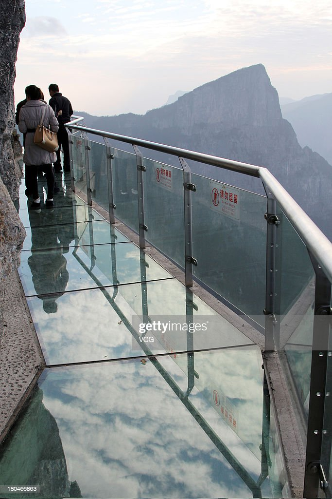 Tourists walk on a glass road alongside a cliff on Tianmen Mountain on November 9, 2011 in Zhangjiajie, Hunan Province of China. The oriental 'Skywalk', 1430m above sea level and is 60 meters long. It was built along west cliff at the Yunmeng Fairy Summit, the summit of Tianmen Mountain and Zhang Jiajie. In order to keep the glass road clean, tourists are to put on shoe covers before passing.