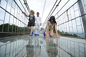 Tourists walk on a suspension bridge made of glass at the Shiniuzhai National Geological Park on September 24 2015 in Pingjiang County China The...