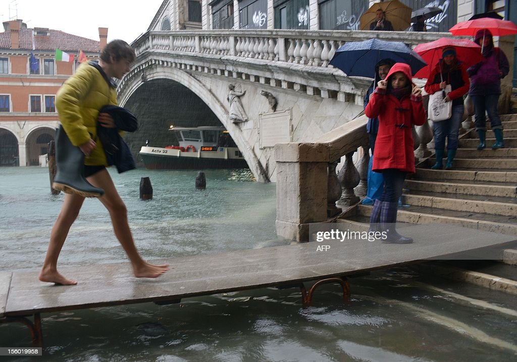 Tourists walk on footbridges near the Rialto bridge during a 'acqua alta' on November 11, 2012 in Venice. Rain and wind hit the north of Italy on Sunday and the folooding reached 150 centimetres in Venice. AFP PHOTO / MARCO SABADIN