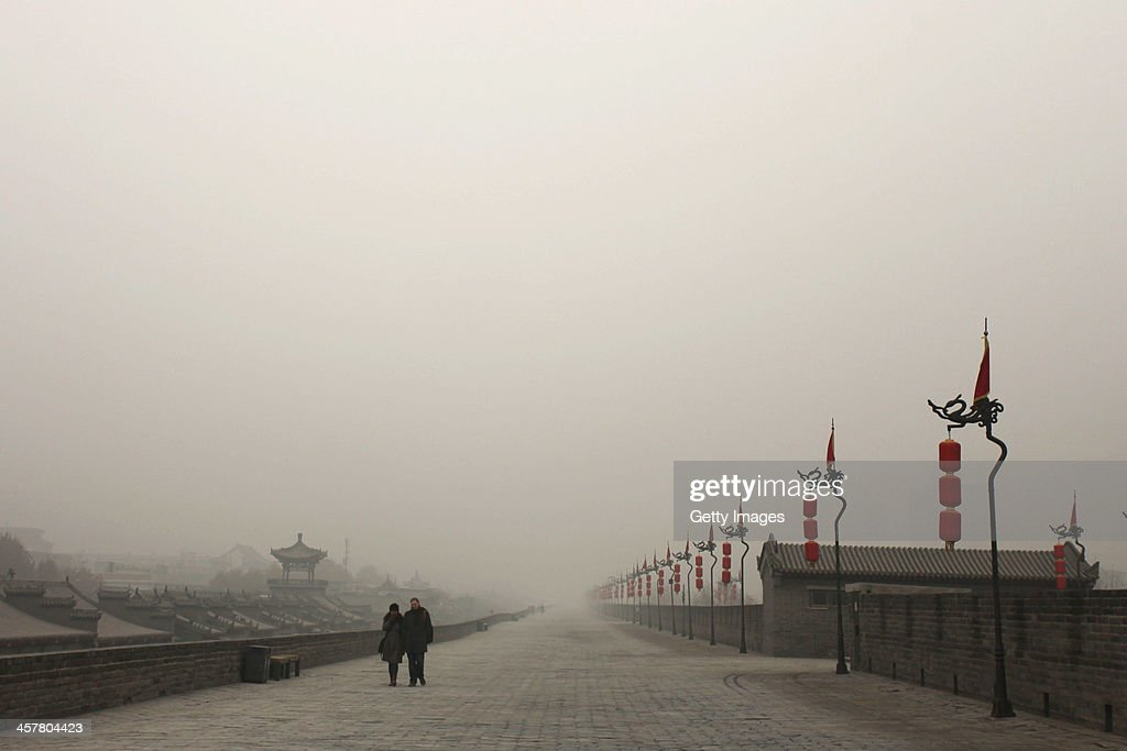 Tourists walk on the city wall as heavy smog engulfs the city on December 18, 2013 in Xi An, China. Heavy smog has shrouded Xi'an for two days, and local environment agency advised people to stay indoors.