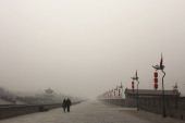 Tourists walk on the city wall as heavy smog engulfs the city on December 18 2013 in Xi An China Heavy smog has shrouded Xi'an for two days and local...