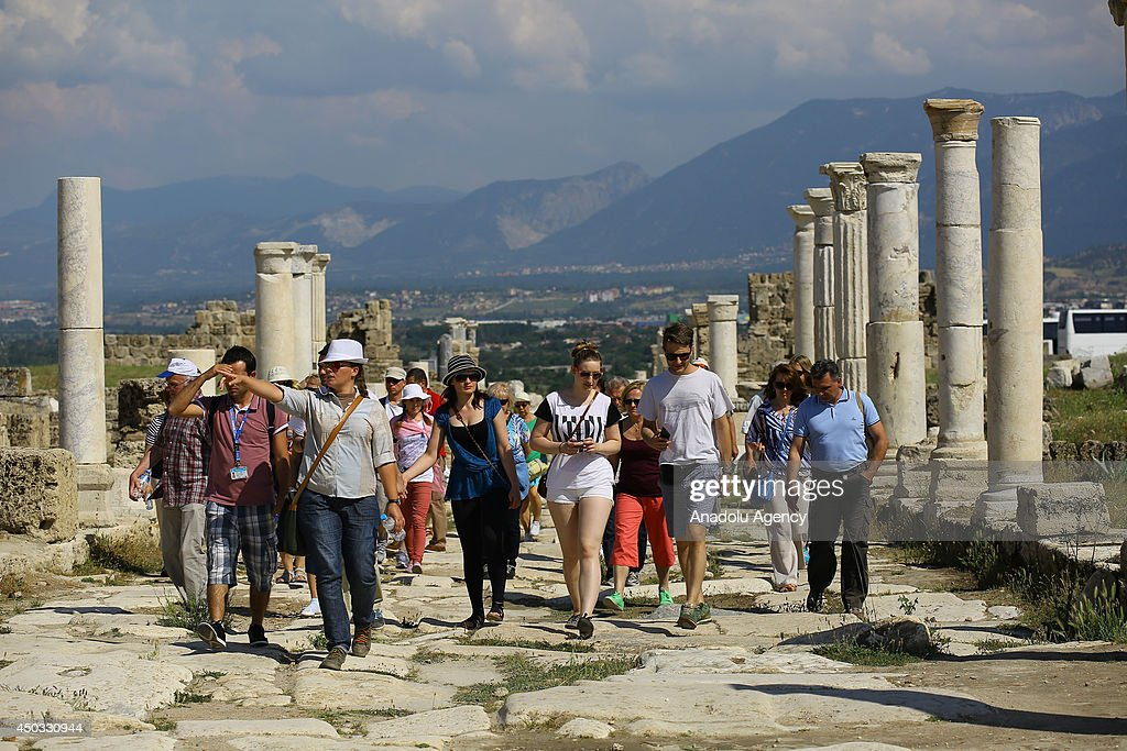 Tourists walk on the colonnaded street in Laodikia Antique City which is famous for its ancient stadium, baths, temples, gymnasium, theatres, and houses in Denizli province of Turkey on June 9, 2014. Laodikeia earlier known as Diospolis and Rhoas was the ancient metropolis of Phrygia Pacatiana built on the river Lycus. Laodicea on the Lycus is the building of which is ascribed to Antiochus II Theos, in 261-253 BC, in honor of his wife Laodice and destroyed during the invasions of the Turks and Mongols after 1230.