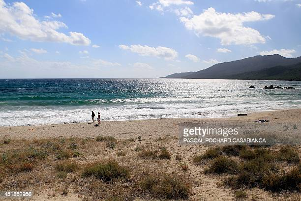 Tourists walk on the Cupabia beach on July 8 2014 in CotiChiavari on the French Mediterranean island of Corsica Usually crowded in the summertime the...