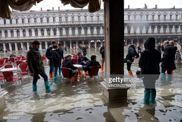 Tourists walk on the flooded St Mark's Square during an ''acquaalta'' alert in Venice on February 1 2014 The rise in the water level is due to winds...