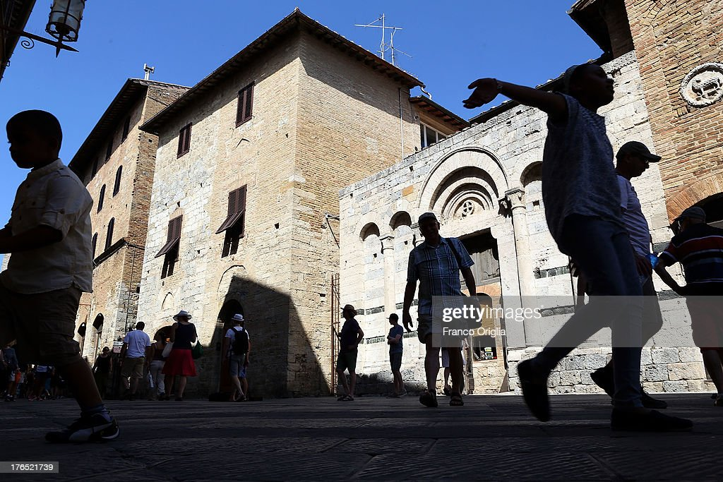 Tourists walk on the main street of San Gimignano on August 14, 2013 in San Gimignano, Italy. San Gimignano is a small walled medieval hill town in the province of Siena, Tuscany. Known as the Town of Fine Towers, San Gimignano is famous for its medieval architecture, unique in the preservation of about a dozen of its tower houses.