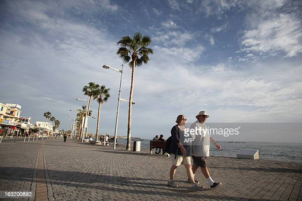 Tourists walk on the pedestrian seafront promenade of the Cypriot resort of Paphos on January 24 2013 AFP PHOTO/YIANNIS KOURTOGLOU