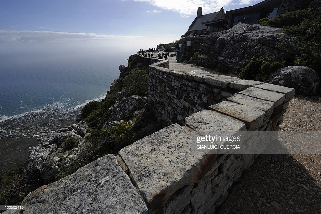 Tourists walk on the south side of Table Mountain at the arrival station of the Table mountain cableway on May 7, 2010 in Cape Town, South Africa. Table Mountain cableway has been running for over 80 years and the cars feature a floor which can rotate while ascending to give passengers a 360 degree panoramic views.