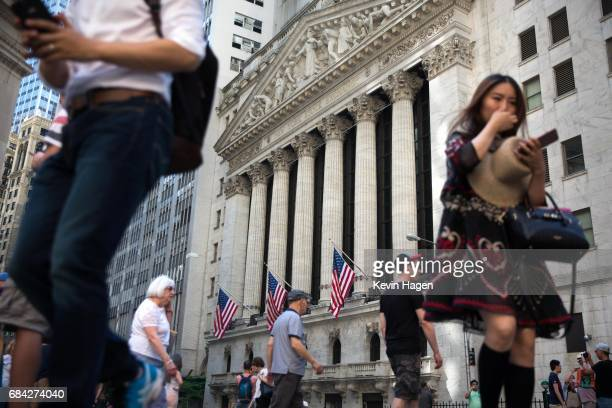 Tourists walk on Wall Street after markets took a sharp turn downward after news reports of former FBI Director James Comey's interactions with...