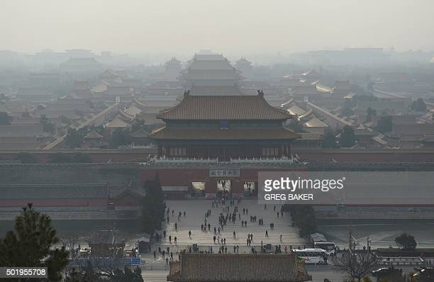 Tourists walk out of the Forbidden City on a polluted day in Beijing on December 19 2015 The Chinese capital issued its secondever red alert for...