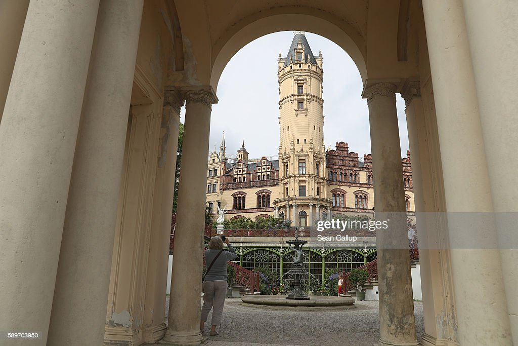 Tourists walk outside Schloss Schwerin castle seat of the state parliament of the state of MecklenburgWestern Pomerania and also a UNESCO Wolrd...