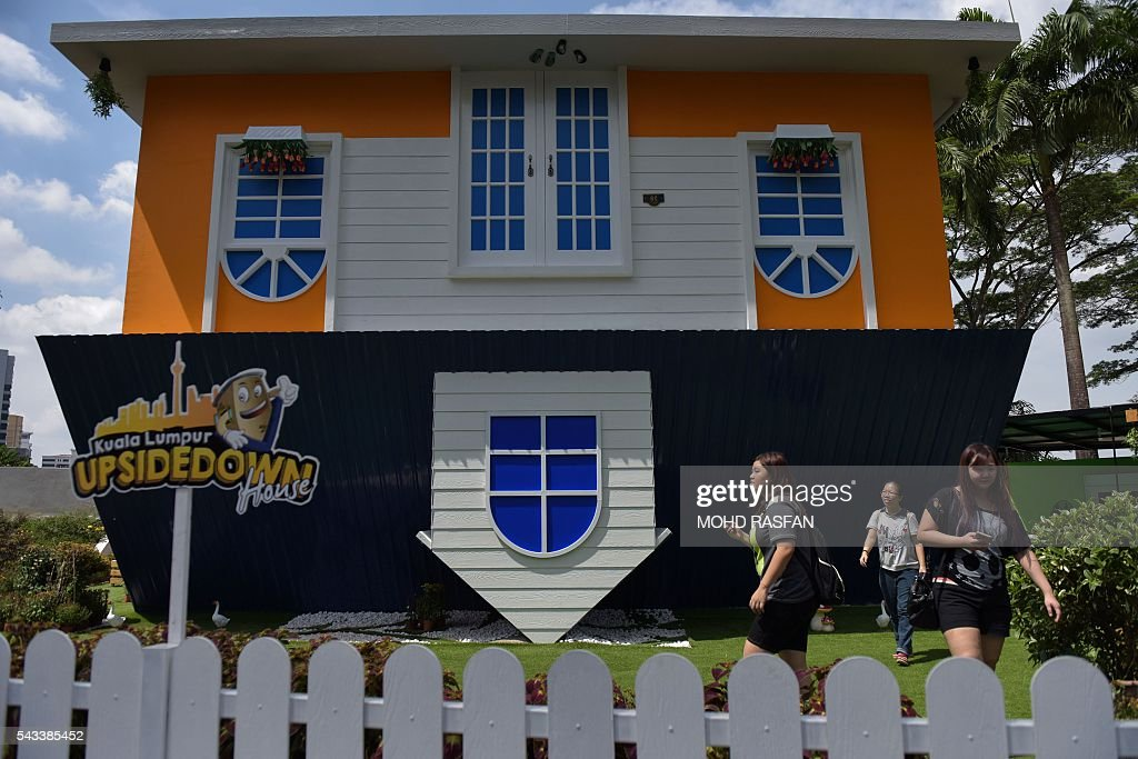 Tourists walk outside the Kuala Lumpur Upside Down House at KL Tower in Kuala Lumpur on June 28, 2016. Kuala Lumpur Upside Down House is a two-storey house and is the latest attraction for tourists arriving to the Malaysian capital where everything inside such as the furniture are placed in an upside down position. / AFP / MOHD
