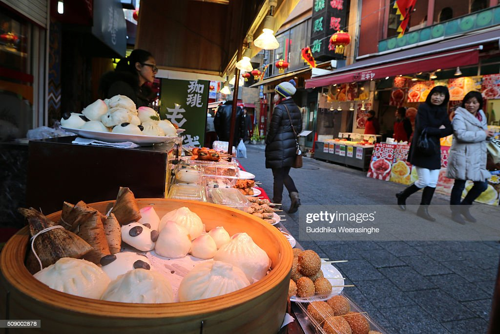 Tourists walk pass the Chinese meat buns stall at the Nankinmachi China Town on February 8, 2016 in Kobe, Japan. In Nankinmachi, the district known as Kobe Chinatown, tourists enjoyed Chinese food, lion dance and the parade organized to celebrate the Lunar New Year.