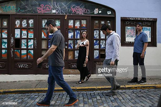 Tourists walk past a boarded up business in Old San Juan a day after the Puerto Rican Governor Alejandro Garcia Padilla gave a televised speech...