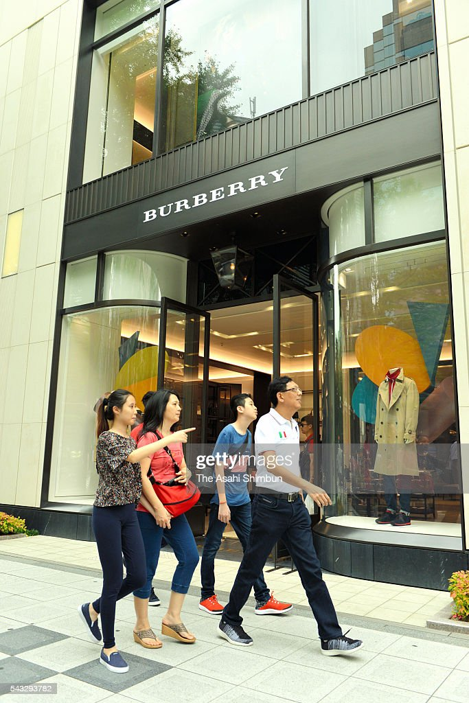 Tourists walk past a Burberry shop on June 27, 2016 in Osaka, Japan. Japanese government and the central bank held a meeting to measure the impact of the 'Brexit'.