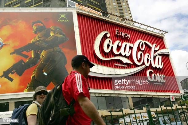 Tourists walk past a giant CocaCola billboard at Kings Cross in Sydney 10 February 2005 CocaCola Amatil announced a 44 percent jump in net profits to...