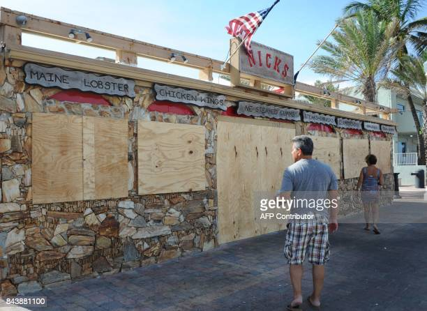 Tourists walk past a restaurant closed in preparation for hurricane Irma in Fort Lauderdale Florida on September 7 2017 Hurricane Irma will have a...
