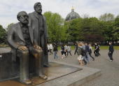 Tourists walk past a sculpture featuring Karl Marx and Friedrich Engels in the centre of Berlin on April 28 2009 Due to the construction of a new...