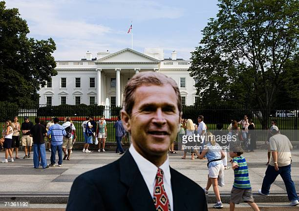 Tourists walk past a standee of US President George W Bush on Pennsylvania Avenue in front of the White House July 3 2006 in Washington DC Peace...
