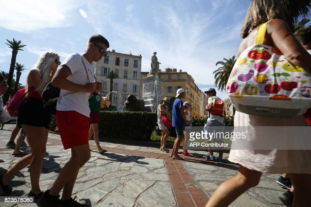 Tourists walk past a statue of Napoleon Bonaparte in central Ajaccio on the French Mediterranean island of Corsica on July 27 2017 Two cruise ships...