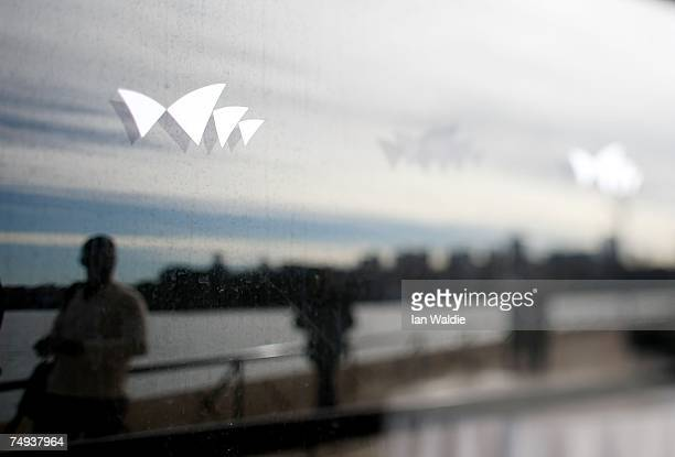 Tourists walk past a window displaying the logo of the Sydney Opera House June 28 2007 in Sydney Australia The Opera House designed by Joern Utzon...