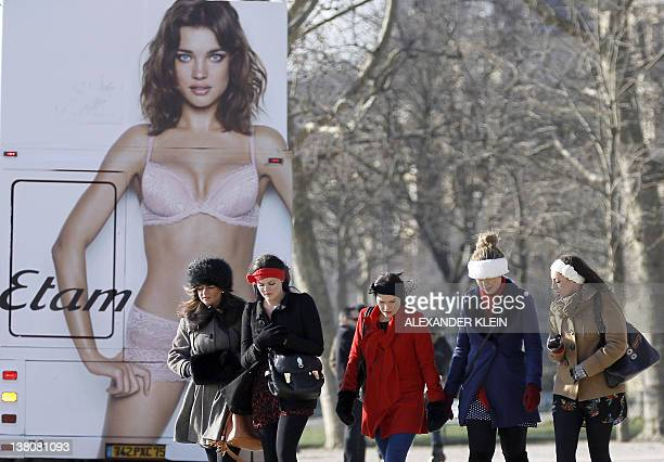 Tourists walk past an advertising billboard on a bus showing Russian former model Natalia Vodianova for Etam Lingerie on February 2 2012 in Paris AFP...
