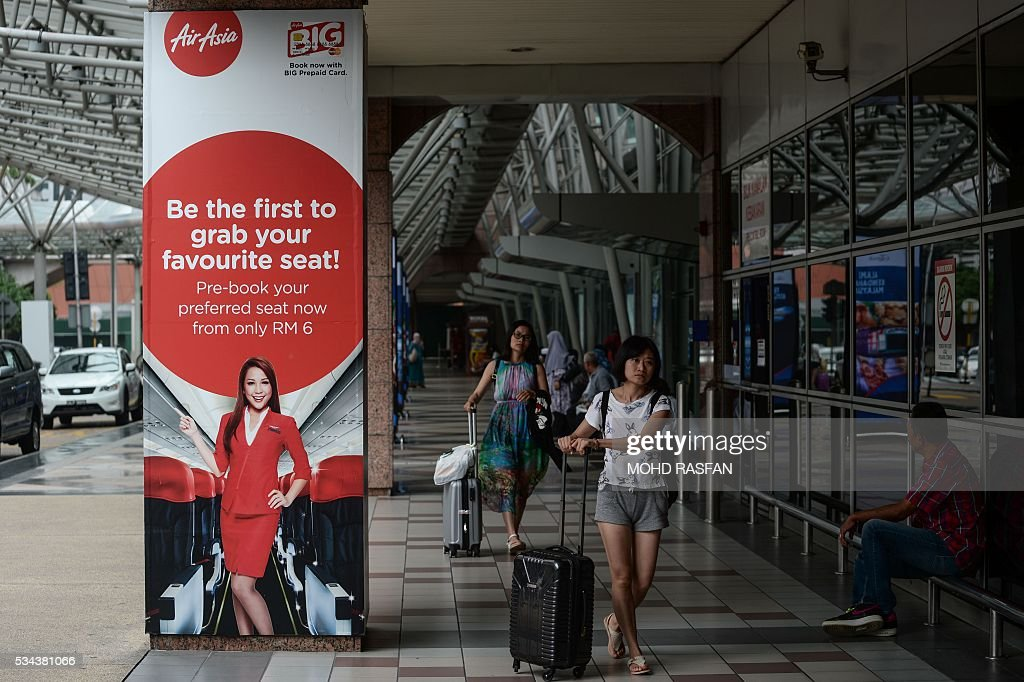Tourists walk past an AirAsia advertisement at Kuala Lumpur Sentral railway station in Kuala Lumpur on May 26, 2016. Malaysia's Budget carrier AirAsia was expected to announce its first quarter results on the back of lower oil prices on May 26. / AFP / MOHD