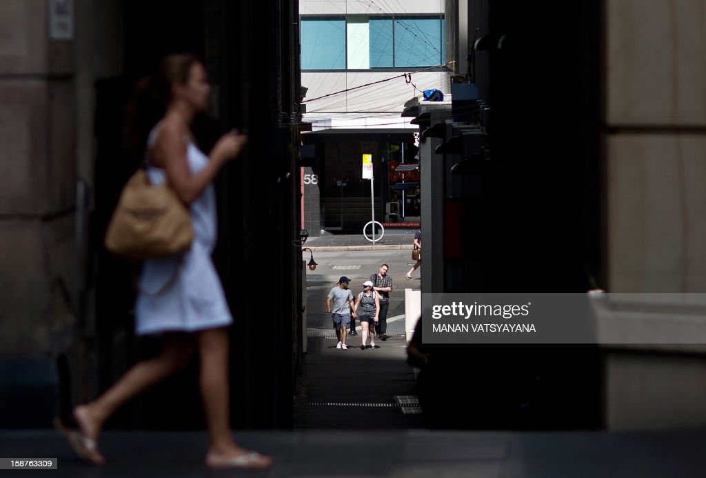 Tourists walk past an alley on the main shopping street in Sydney on December 28, 2012. International visitors to Australia are expected to increase from over 5.9 million in 2010/11 to nearly 8.2 million in 2020/21, an average annual growth rate of 3 percent as reported from Tourism Research Australia (TRA). AFP PHOTO / MANAN VATSYAYANA