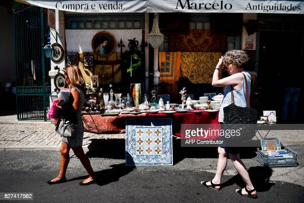 Tourists walk past an antique shop at 'Feira da Ladra' market displaying a tiles' panel for sale in Lisbon on July 1 2017 They used to adorn...