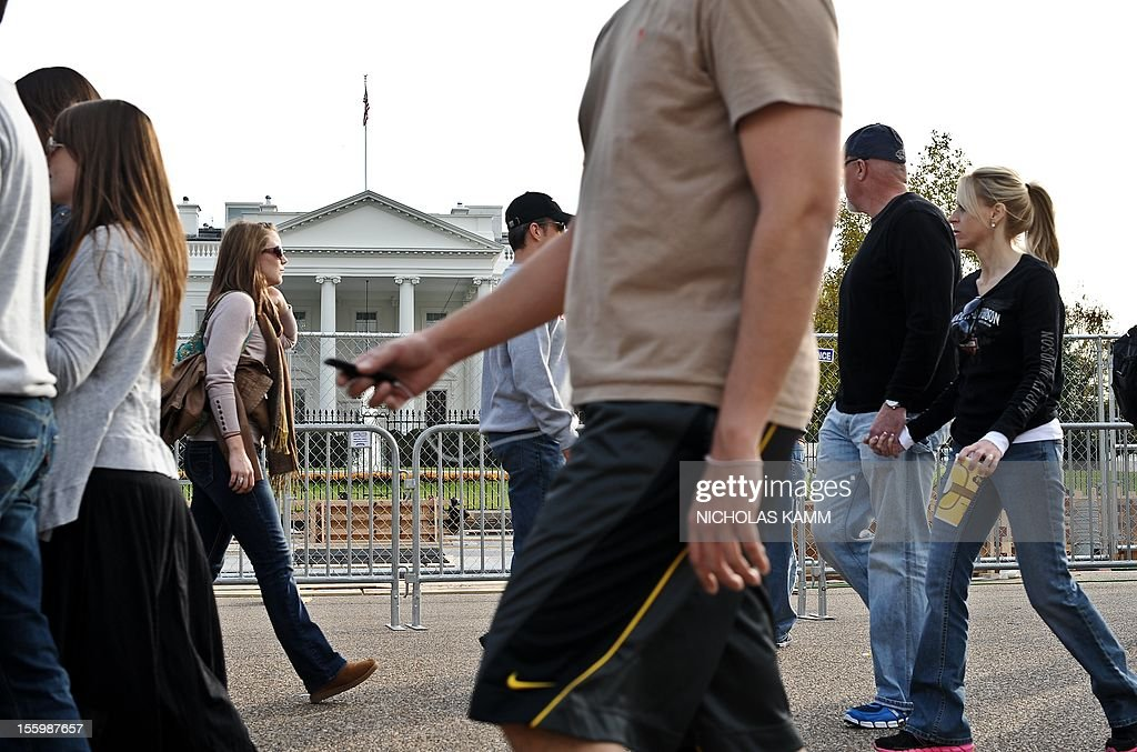 Tourists walk past construction for US President Barack Obama's second inauguration is under way in front of the White House in Washington on November 10, 2012. Obama won Florida's 29 electoral votes in the presidential election on November 10, further fattening his substantial margin of victory in what had been predicted to be a close race. The state was the last to report its tally from the election November 6, in which Obama beat Republican Mitt Romney. With Florida's votes in the electoral college, the president's total goes up to 332, against 206 for Romney. AFP PHOTO/Nicholas KAMM