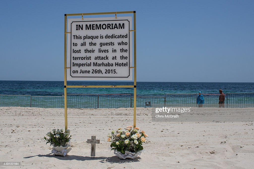 Tourists walk past flowers placed by tourists underneath a memorial sign on the beach in front of the Imperial Marhaba hotel on June 26, 2016 in Sousse, Tunisia. Today marks the one year anniversary of the Sousse Beach terrorist attack, which killed 38 people including 30 Britons. Before the 2011 revolution, tourism in Tunisia accounted for approximately 7% of the country's GDP. The two 2015 terrorist attacks at the Bardo Museum and Sousse Beach saw tourism numbers plummet even further forcing hotels to close and many tourism and hospitality workers to lose their jobs.