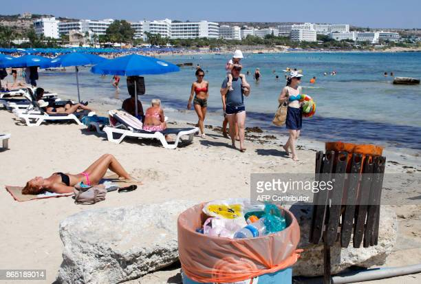 Tourists walk past garbage bins at the beach in the resort town of Ayia Napa in southeastern Cyprus on September 7 2017 With more visitors heading to...