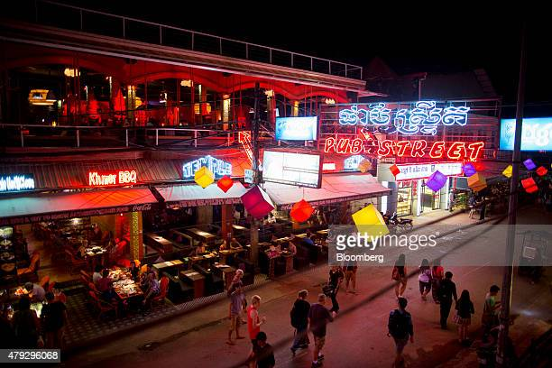 Tourists walk past restaurants and bars on Pub Street at night in Siem Reap Cambodia on Friday June 26 2015 Angkor in the northern province of Siem...