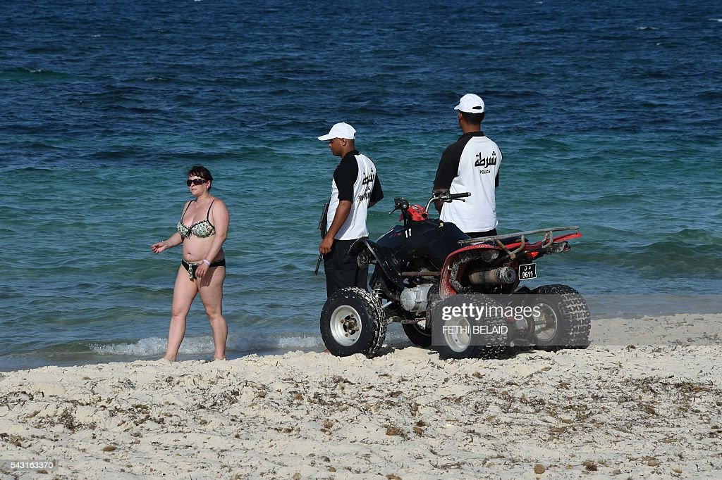 Tourists walk past Tunisian security in the Marhaba Beach in Port el-Kantaoui, on the outskirts of Sousse south of the capital Tunis on June 26, 2016, on the first anniversary of an attack by a jihadist gunman in which 38 people were killed. Tourists fled in horror on June 26, 2015 as a Tunisian gunman pulled a Kalashnikov rifle from inside a furled beach umbrella and went on a shooting spree outside the five-star hotel. / AFP / FETHI