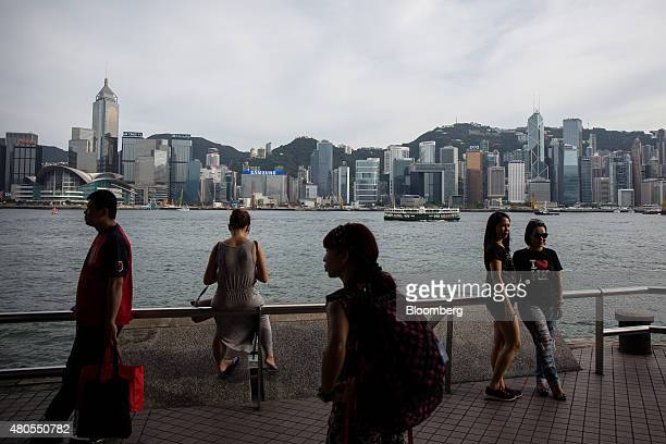 Tourists walk past Victoria Harbour in the Tsim Sha Tsui district as buildings stand in the background on Hong Kong island in Hong Kong China on...