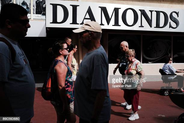 Tourists walk through a shopping district after arriving on a cruise ship in St John's on December 11 2017 in St John's Antigua While its sister...