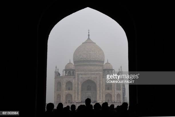 TOPSHOT Tourists walk through an archway during their visit to the Taj Mahal monument in the Indian city of Agra on January 7 2017 FAGET