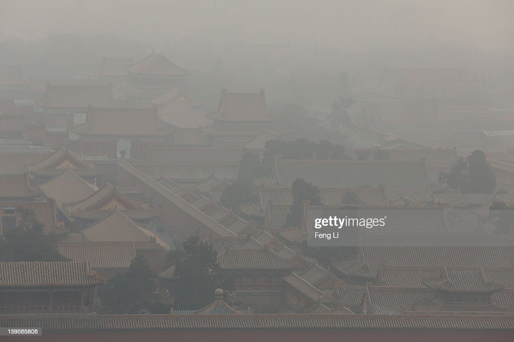 Tourists walk through the door of the Forbidden City as pollution covers the city on January 16, 2013 in Beijing, China. Heavy smog shrouded Beijing with pollution at hazardous levels from January 12.