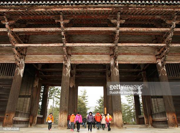 Tourists walk through the entrance of the Todaiji Temple on March 2 2013 in Nara Japan The Buddhist Todaiji temple was built in 752 AD and is now one...