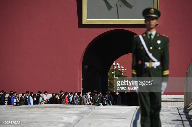 Tourists walk through Tiananmen Gate as a paramilitary policeman stands guard in front of the portrait of late communist leader Mao Zedong in Beijing...