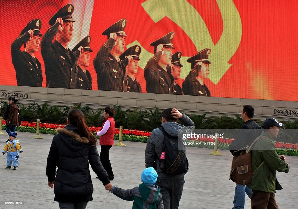 Tourists walk through Tiananmen Square on the eve of the Chinese Communist Party's congress to elect a new leader in Beijing on November 7 2012 The...