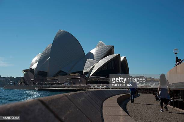 Tourists walk towards the landmark Opera House at the Circular Quay in Sydney Harbour on June 11 2013 AFP PHOTO / SAEED KHAN / AFP / SAEED KHAN