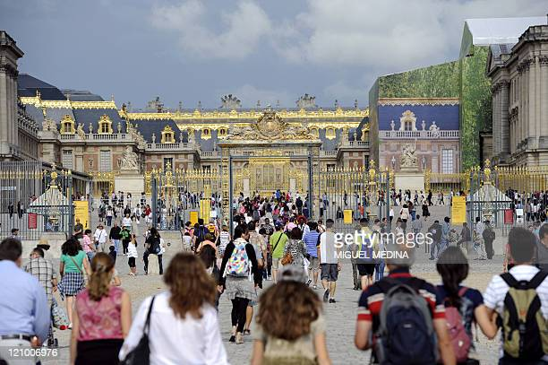 Tourists walk towards the palace of Versailles on August 3 2011 in the French town of Versailles a southwestern suburb of Paris Some 15 millions...
