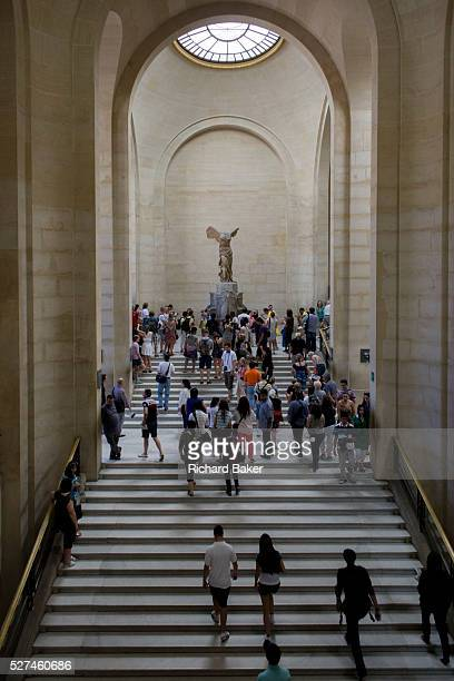 Tourists walk towards The Winged Victory of Samothrace also called the Nike of Samothrace a 2nd century BC marble sculpture of the Greek goddess Nike...