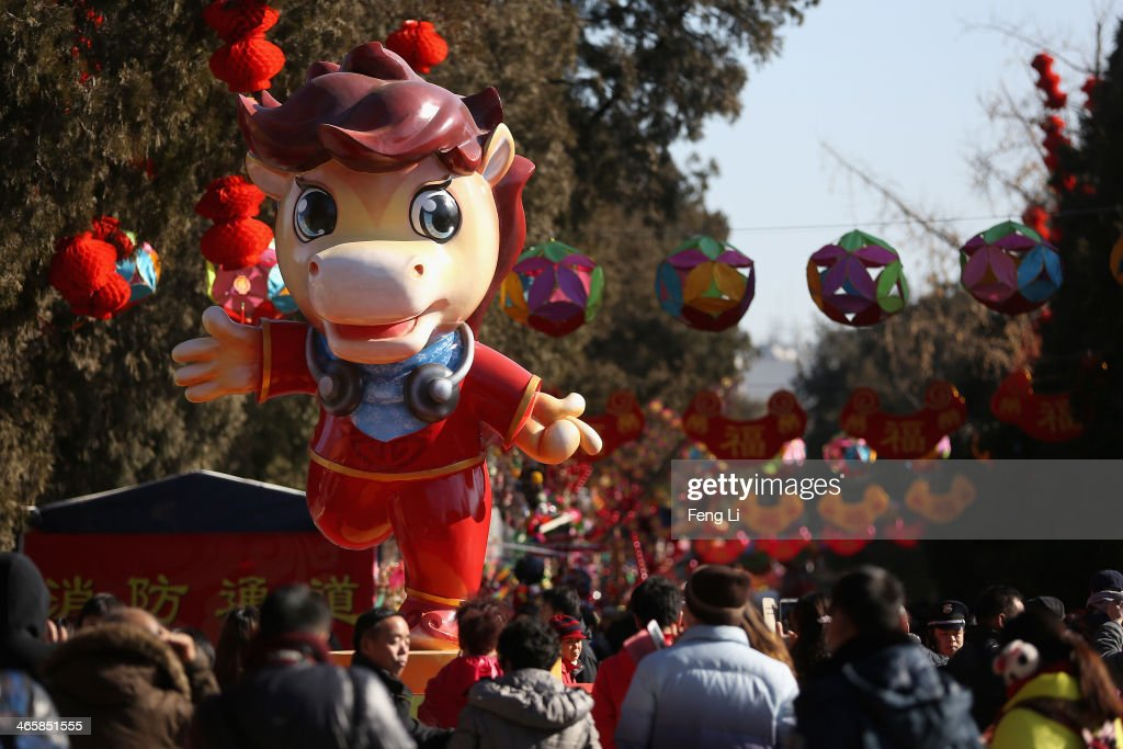 Tourists walk under a horse sculpture at the Spring Festival Temple Fair for celebrating Chinese Lunar New Year of Horse at the Temple of Earth park on January 30, 2014 in Beijing, China. The Chinese Lunar New Year of Horse also known as the Spring Festival, which is based on the Lunisolar Chinese calendar, is celebrated from the first day of the first month of the lunar year and ends with Lantern Festival on the Fifteenth day.