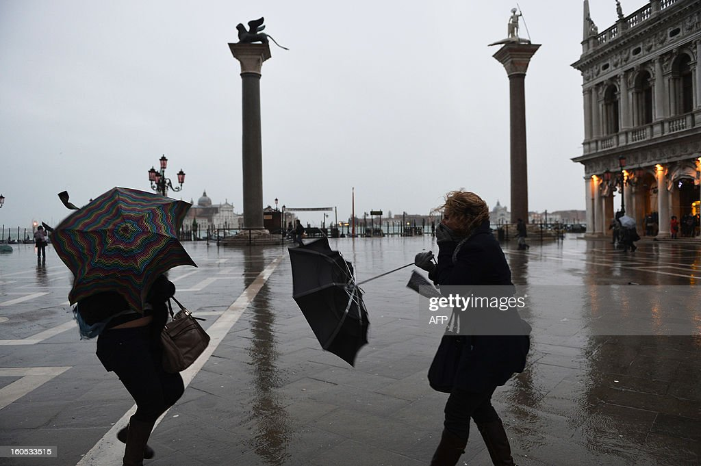 Tourists walk under the rain and a heavy wind at St Mark's square during the carnival on February 2, 2013 in Venice. The 2013 edition of the Venice carnival is untitled ' Live in Colour' and runs from January 26 to February 12. AFP PHOTO / VINCENZO PINTO