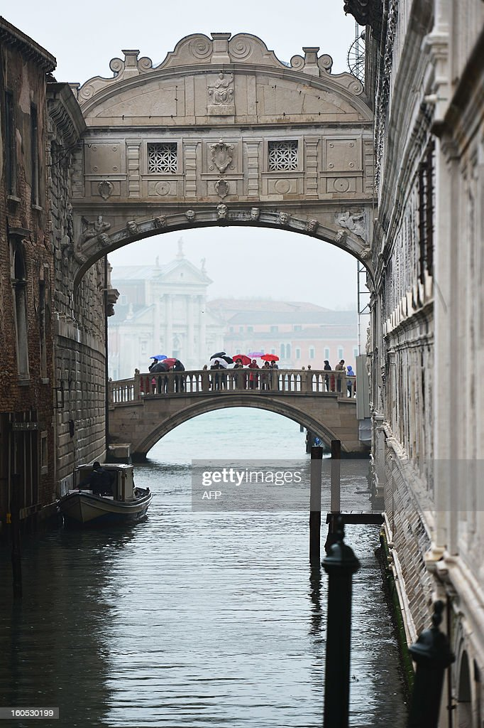 Tourists walk under the rain on the bridge of sighs during the carnival on February 2, 2013 in Venice. The 2013 edition of the Venice carnival is untitled ' Live in Colour' and runs from January 26 to February 12.